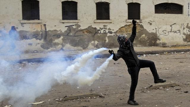 An Egyptian 'Black Bloc' protestor throws a tear gas canister toward a police line. (Facebook)