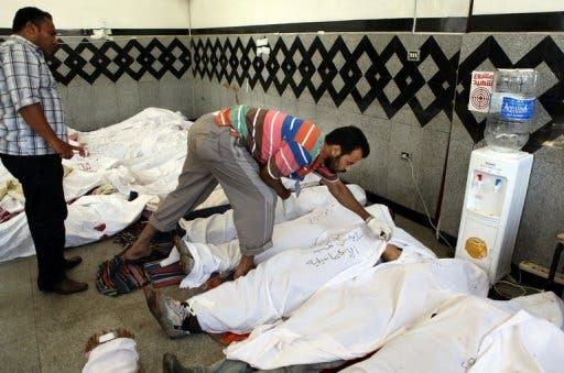 Men check the IDs of dead Muslim Brotherhood supporters, at a field hospital in Cairo, on July 27, 2013 (AFP)