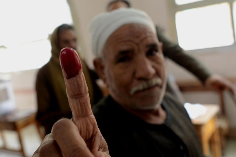 An Egyptian man shows his ink-stained finger after casting his vote on a new constitution at a polling station in Cairo on January 14, 2014. (AFP)