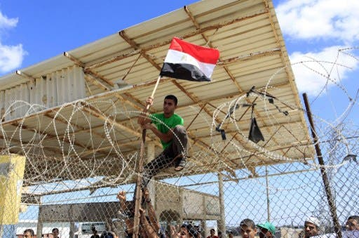 A Palestinian protestor puts up an Egyptian flag on barbed wire during a rally in front of the Rafah border crossing in the southern Gaza Strip on September 16, 2013. (AFP)