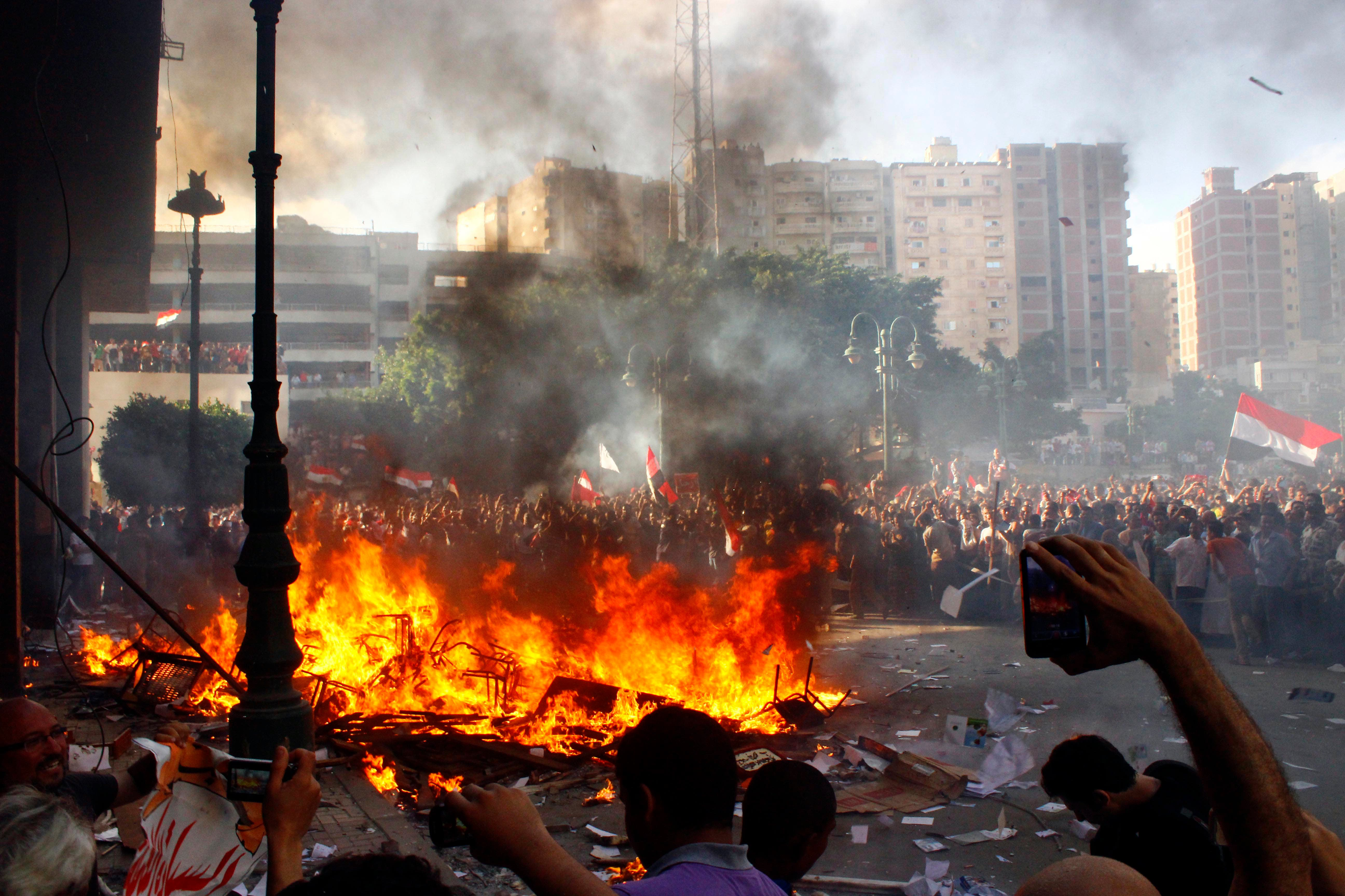 Opponents of Egyptian President Mohamed Morsi burn the content of a Freedom and Justice Party office in the coastal city of Alexandria on June 28, 2013. One person was killed and more than 70 injured in Egypt's second city of Alexandria on Friday as clashes raged between supporters and opponents of Islamist President Mohamed Morsi, state media reported. (Source: AFP)