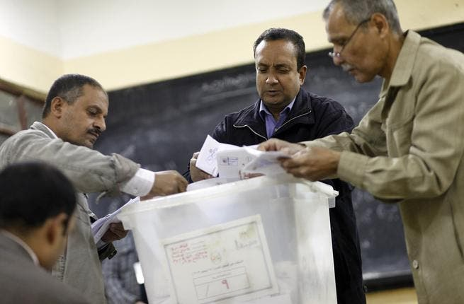 Polling station officials count ballots in Cairo on Saturday at the end of the first day of vote in a referendum on a new constitution. (AFP PHOTO/MAHMOUD KHALED)