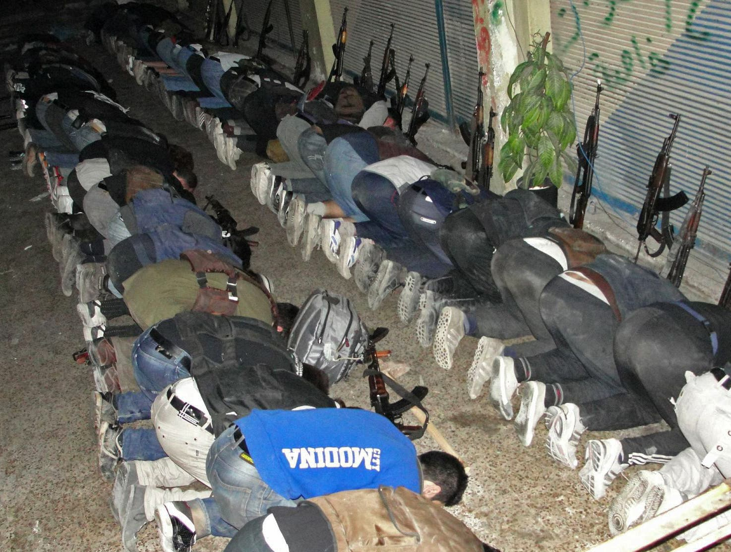 A handout picture released by the opposition-run Shaam News Network on June 21, 2013 shows rebel fighters praying in Syria's central city of Homs on June 17. (AFP/MOHAMMED IBRAHIM / SHAAM NEWS NETWORK