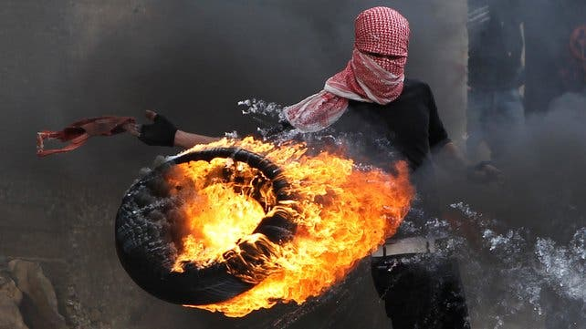 A Palestinian sets fire to a tyre during clashes between hundreds of Palestinians and Israeli soldiers earlier this year in Hebron. (file AFP)