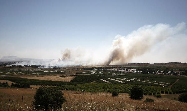 Smoke billows during clashes between Syrian rebels and forces loyal to the regime near the Quneitra crossing in the Golan Heights on Thursday. AFP Photo