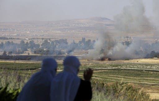 Two stray mortary shells from Syria hit the Israel-occupied Golan Heights on Thursday. Druze women from Israel watch mortar shells exploding in the Golan Heights in June. (AFP/File)