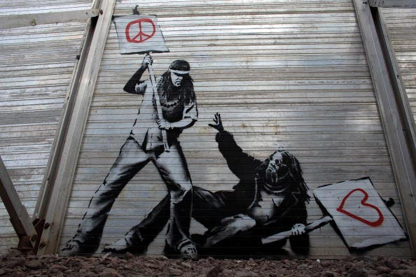 Art work said to be by underground artist Banksy is seen on the fence at the Glastonbury Festival site at Worthy Farm, Pilton on June 24, 2010 in Glastonbury, England.