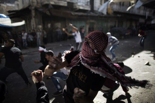 Palestinian stone throwers confront Israeli soldiers in the southern West Bank city of Hebron on September 23, 2013, as tensions run high following the death of an Israeli soldier. (AFP)