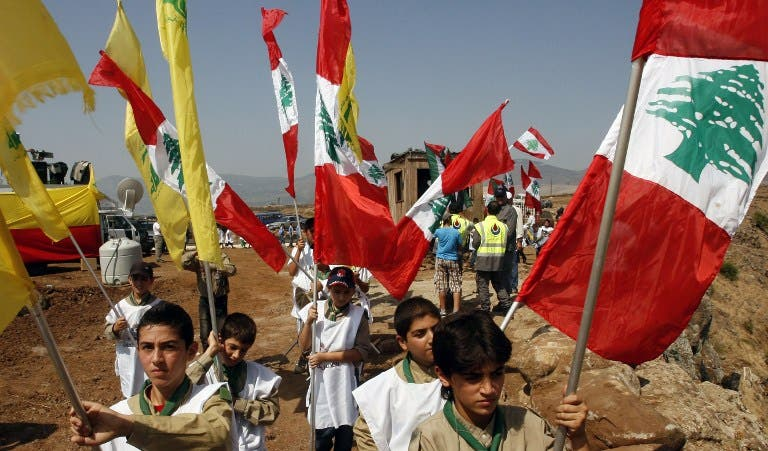 Young boys of Hezbollah's al-Mehdi scouts wave Lebanese and Hezbollah flags during a parade in the southern area of Wazzani river on the Lebanese-Israeli borders, on August 2, 2013. (AFP)