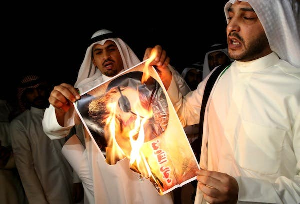 Kuwaiti protesters set ablaze a picture of Hezbollah's chief Hassan Nasrallah during a protest in front the Lebanese embassy against Hezbollah's and Iran's involvement in Syria on Tuesday. AFP photo