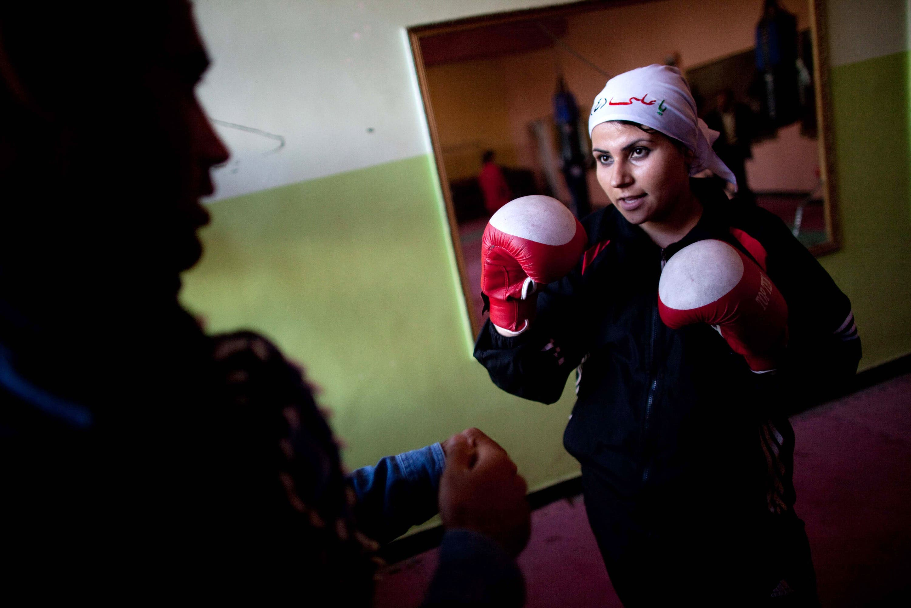 An Afghani woman in a head scarf playing boxing.