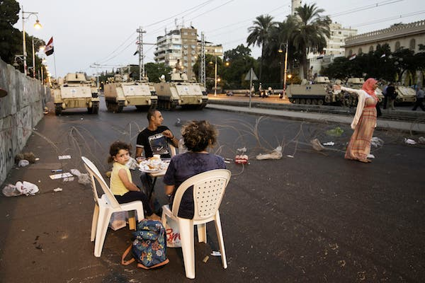 Egyptian army APCs are stationed outside the presidential palace as opponents of ousted president Mohamed Morsi gather to break their fast with the iftar meal in Cairo (Source: AFP/GIANLUIGI GUERCIA)