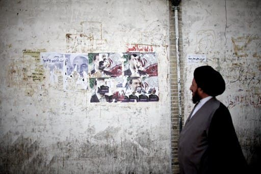 An Iranian clergyman walks past electoral posters of presidential candidates in Qom, south of Tehran, ahead of Friday's elections. AFP image