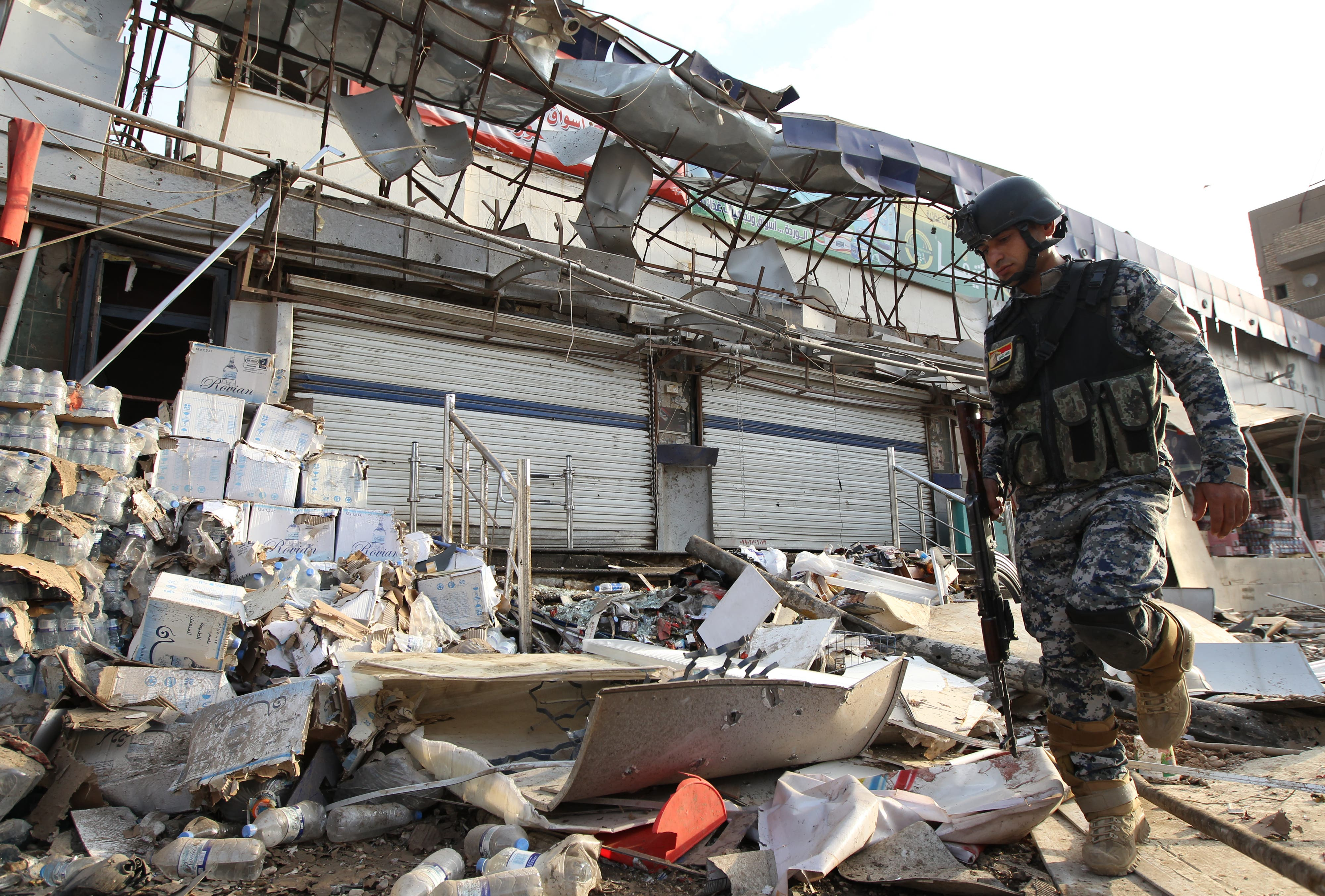 An Iraqi policeman inspects the damage outside a supermarket in central Baghdad's commercial Karrada neighbourhood on June 25, 2013 after a car bomb exploded in the parking area the night before. (Source: AFP/ALI AL-SAADI)