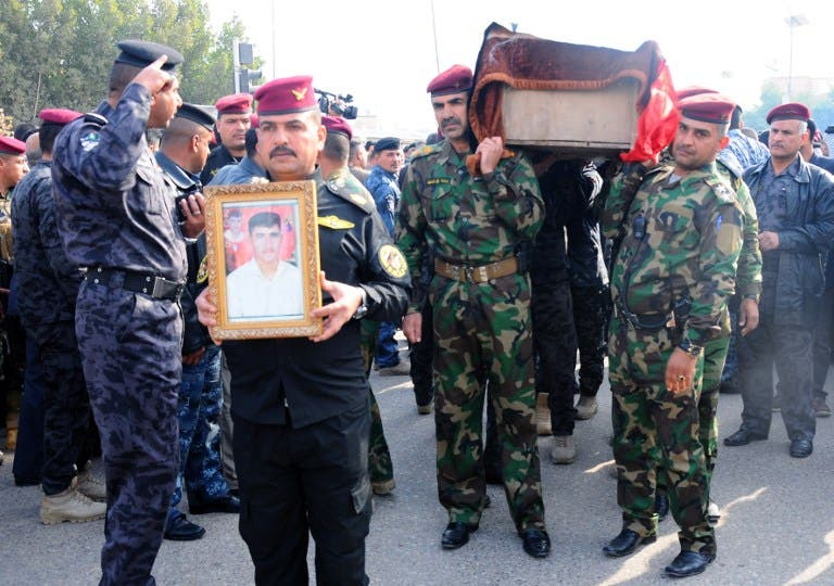 Military officers carry the coffin of a comrade during his funeral in the city of Nasiriyah, on December 31, 2013, after he was killed in fighting in the western Anbar province. (AFP)
