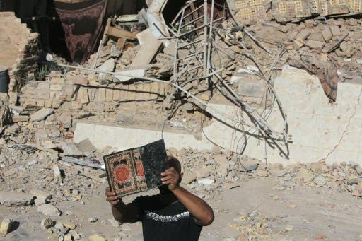 An Iraqi man retrieves a copy of the Koran from the debris of the Al-Hussein mosque following an explosion in the district of al-Musayyib, south of Baghdad on Monday. The Islamic State of Iraq and the Levant on Tuesday claimed responsibility for the attacks. (AFP)
