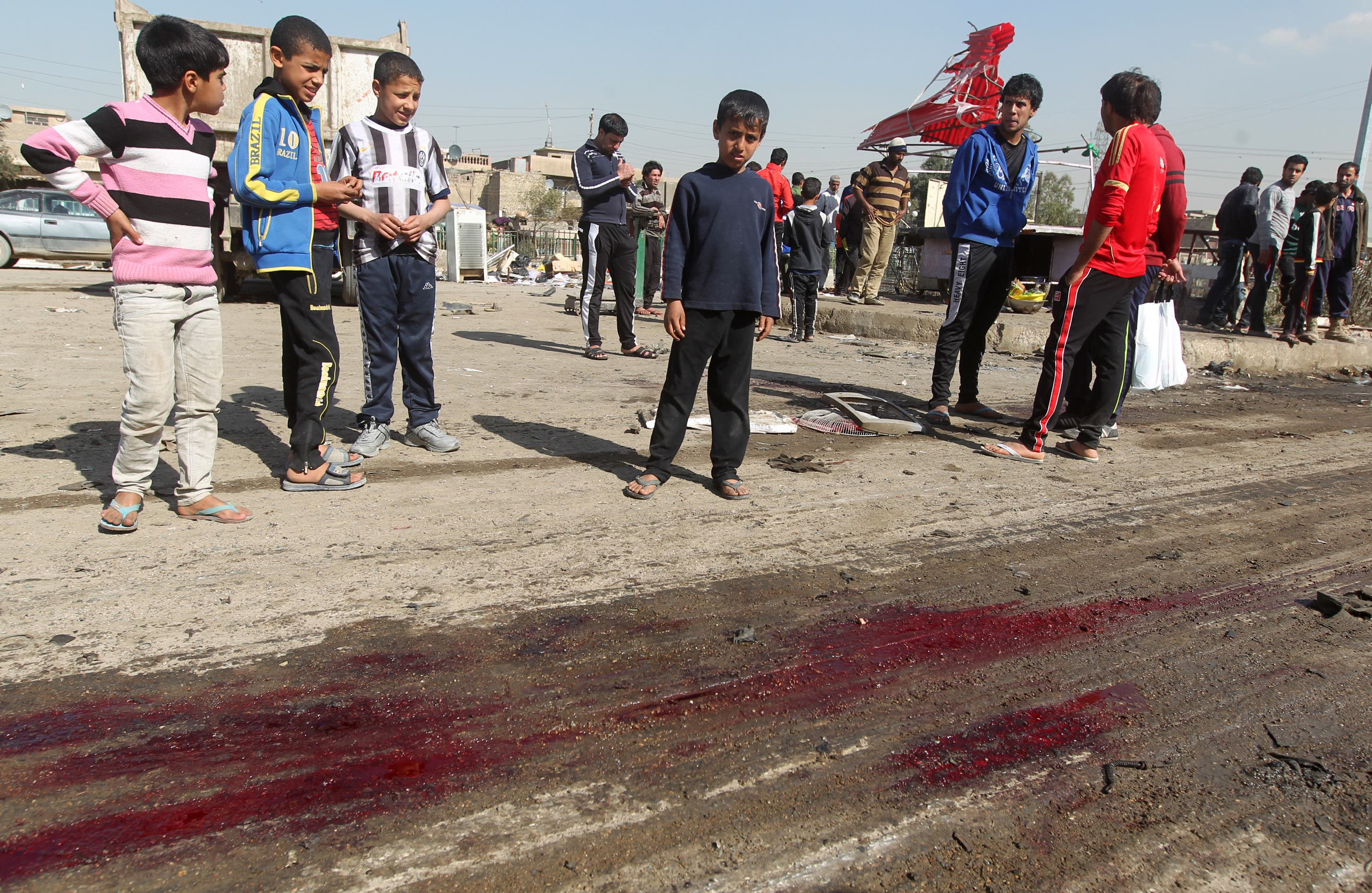 Iraqi children gather around blood stains at the site of a car bomb attack in Baghdad's impoverished district of Sadr City on Sunday. A series of bombings mainly targeting Shiite areas of Baghdad killed at least 21 people, officials said, in the latest violence to hit Iraq as it struggles with protests and a political crisis. (AFP Photo/Ahmad al-Rubaye)