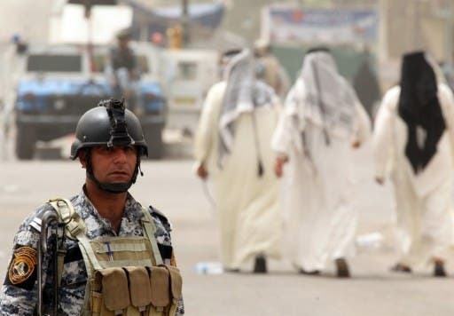 Iraqi troops guard a main road as Shiite Muslim pilgrims (R) walk by him in Baghdad on Tuesday. AFP Photo
