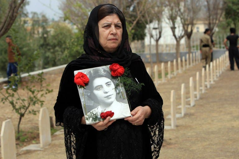 An Iraqi Kurdish woman visits the grave of her sister, who was killed in a gas attack by former Iraqi president Saddam Hussein in 1988 (AFP Photo)
