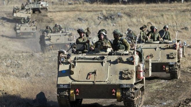 Israeli army Armored Personnel Carriers maneuver during a military exercise near the northern border with Syria on June 25, 2013. (AFP/File)