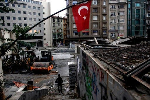 People walk next to Taksim's Gezi Park early on Wednesday in Istanbul, hours after riot police invaded the square. AFP image.