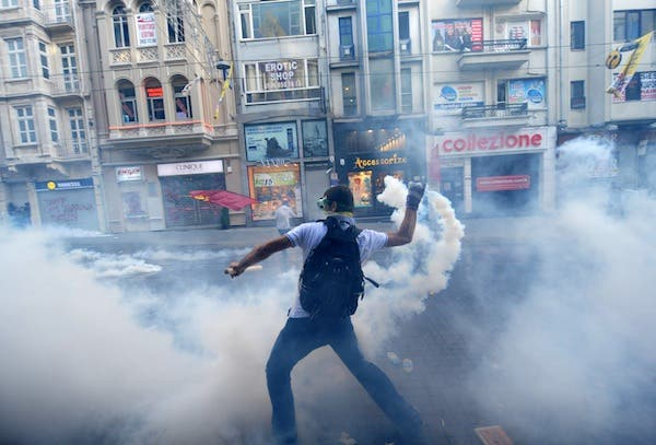 A protestor throws back a canister of tear gas to Turkish riot policemen during a protest against the demolition of Taksim Gezi Park on Friday.  AFP Photo