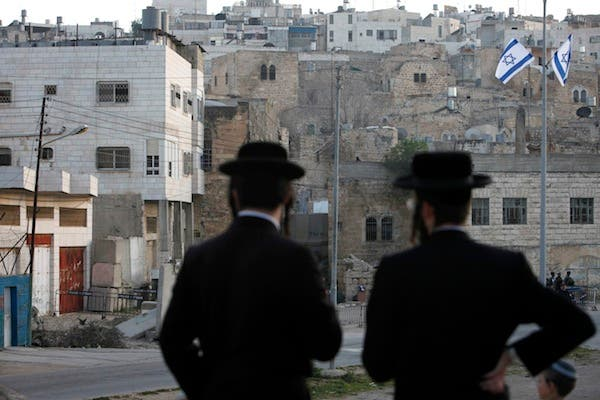 Ultra-orthodox Jews look out over an Israeli settlement on Palestinian territories. (Al Bawaba file photo)