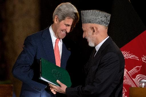 US Secretary of State John Kerry (L) shakes hands with Afghan President Hamid Karzai after a press conference at the Presidential Palace in Kabul on October 12, 2013 (Pool/AFP/File, Jacquelyn Martin)