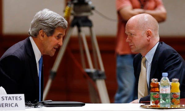 US Secretary of State John Kerry and British Foreign Secretary William Hague discuss Syria at the Friends of Syria meeting in Amman on Wednesday evening