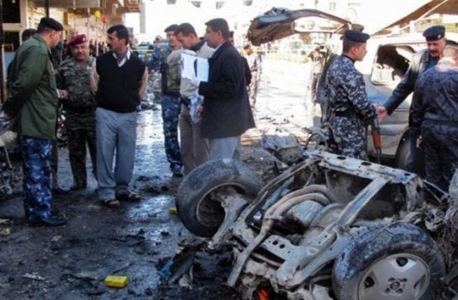 Police inspect the aftermath of a car bomb in Kirkuk