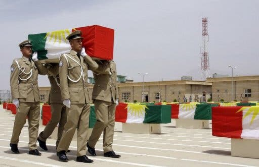 Iraqi Kurdish police officers carry a coffin draped with the Kurdish flag, on May 28, 2012 (AFP/File)