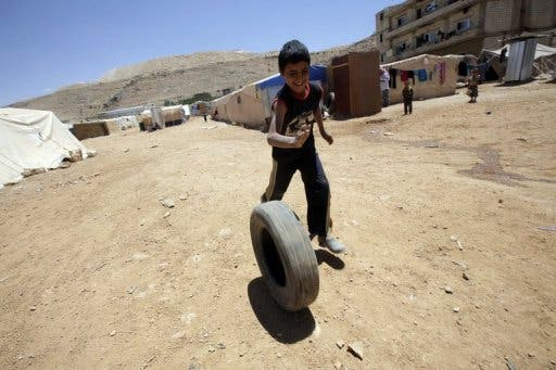 A young Syrian boy plays with a tyre at the Arsal refugee camp on June 14, 2013 in Lebanon (AFP/File)
