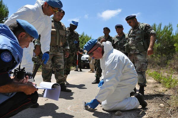 UN experts work at the scene of an explosion that wounded overnight four Israeli soldiers on patrol on August 7, 2013 inside the Lebanese territory along the border with Israel. (AFP)