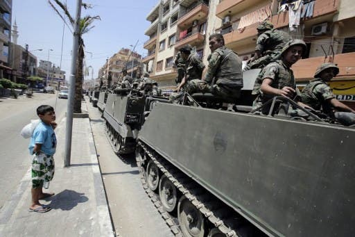 A boy watches Lebanese soliders as they drive between the Sunni and Alawite sections of Tripoli. AFP