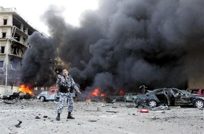 A picture taken on February 14, 2005 shows a Lebanese police officer gesturing on the site of an explosion which killed former Lebanese premier Rafiq Hariri and 21 others in Beirut. The Beirut government is in paralysis, business deals are on hold and tongues abuzz with rumours as Lebanon anxiously awaits indictments by a UN tribunal probing Hariri's murder.