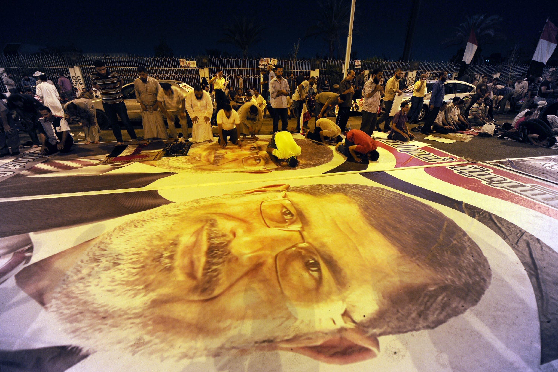 Members of the Muslim Brotherhood pray on posters of ousted Egyptian president Mohamed Mursi (AFP/FAYEZ NURELDINE)