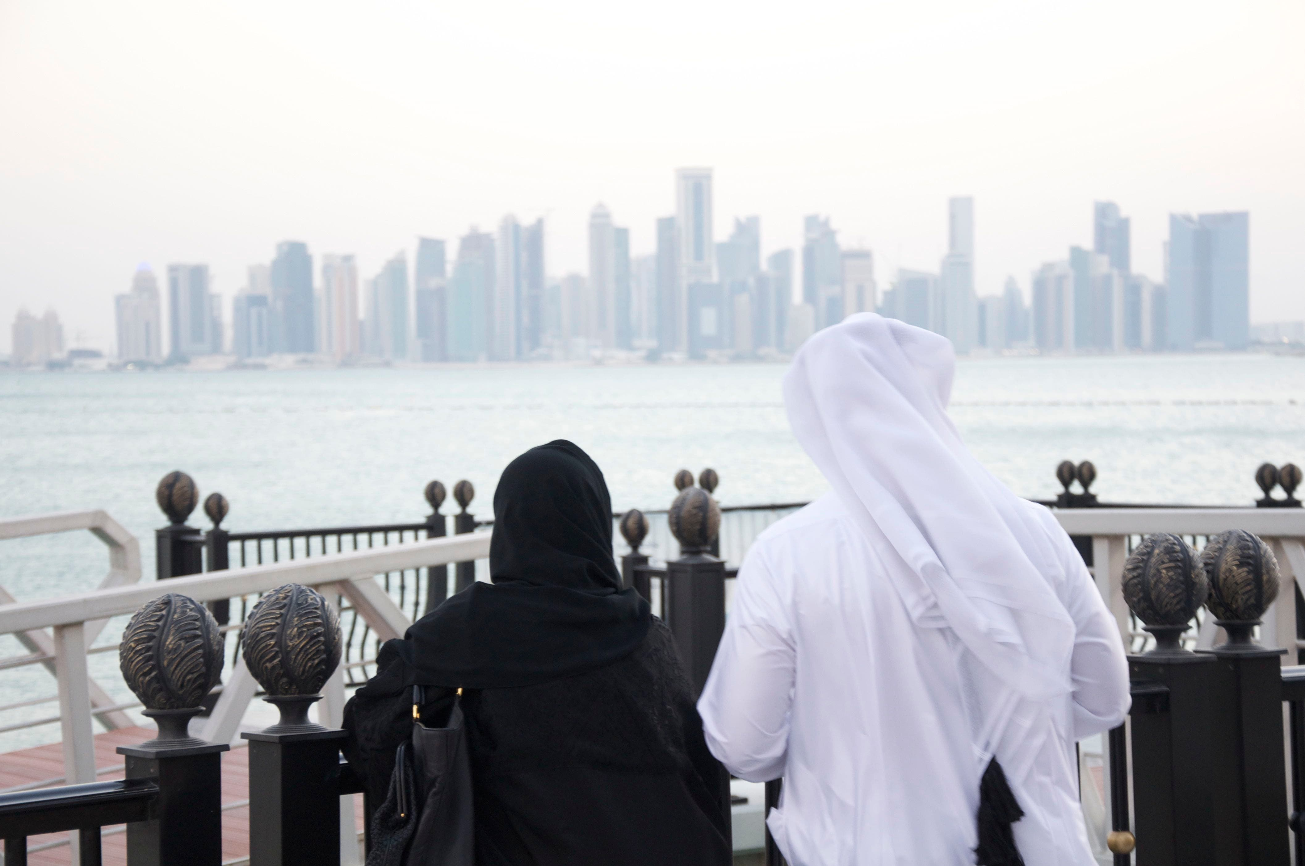 A man and woman look out at the Doha Skyline (Albawaba/J. Zach Hollo)