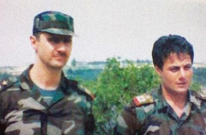 An undated photo showing a young Manaf Tlas (right) next to President Assad