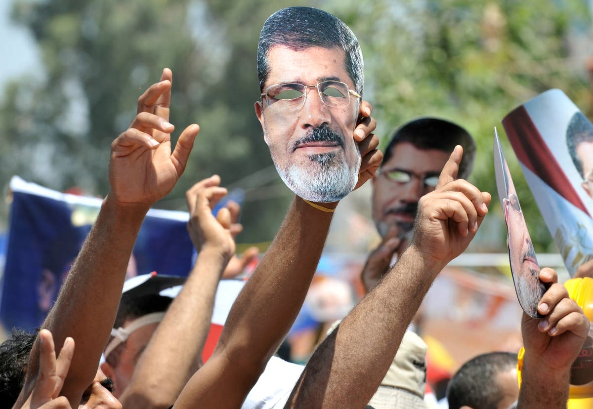 Supporters of deposed president Mohamed Morsi (portrait) shout slogans during a demonstration following Friday prayers in Cairo on July 26, 2013 (AFP)