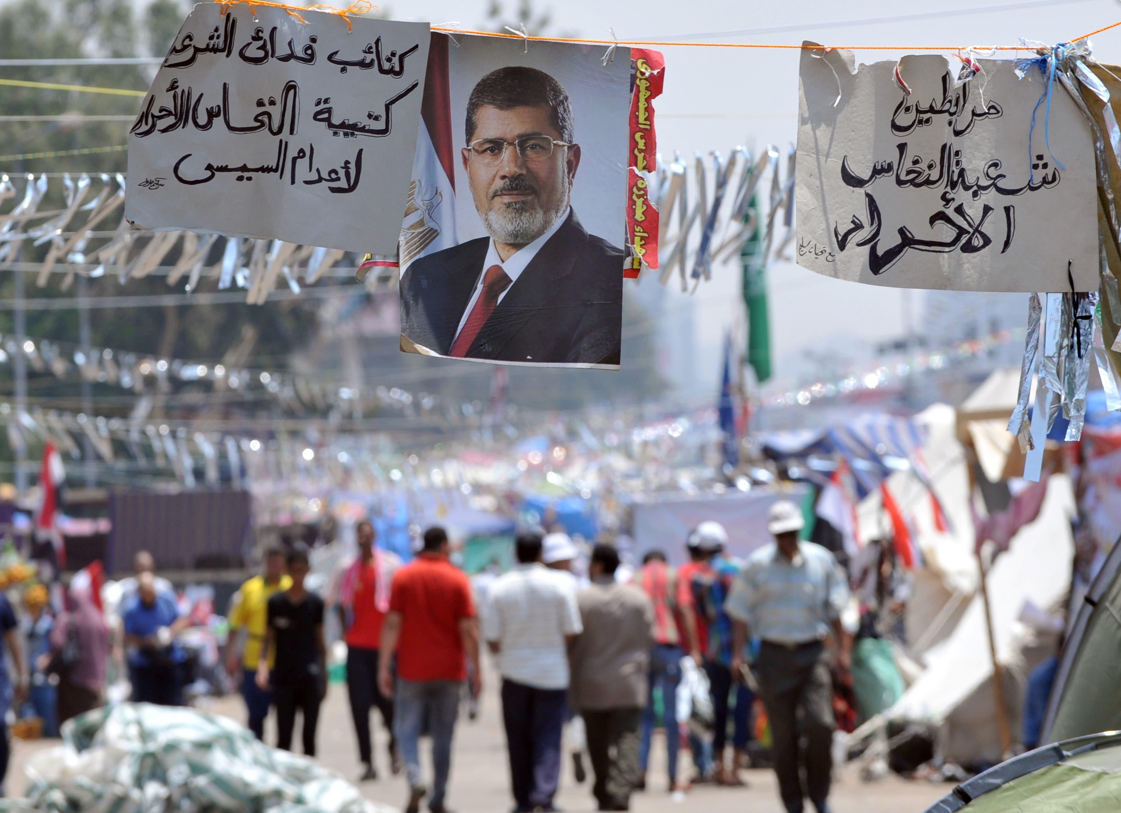Supporters of Egypt's deposed president Mohamed Morsi walk past his portrait in Cairo (AFP/FAYEZ NURELDINE)