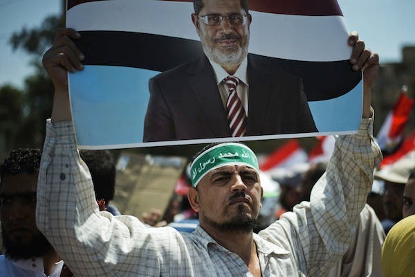 A protester holds a sign of Egyptian president Mohammed Morsi. (Source: AFP)