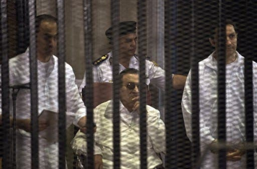 Ousted Egyptian president Hosni Mubarak (C) and his two sons Alaa (R) and Gamal (L) are seen behind the defendents' cage during their retrial at the Police Academy in Cairo on Saturday. The sons have now been released. AFP photo