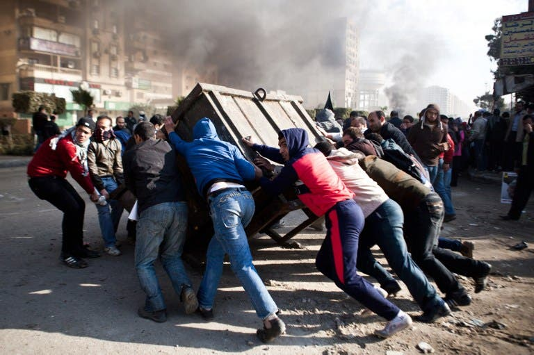 Supporters of ousted president Mohamed Morsi block a street during clashes with Egyptian security forces in Nasr City, Cairo on January 8, 2014. 63 Brotherhood supporters were sentenced to three years in prison on Thursday in a Cairo court. (AFP)