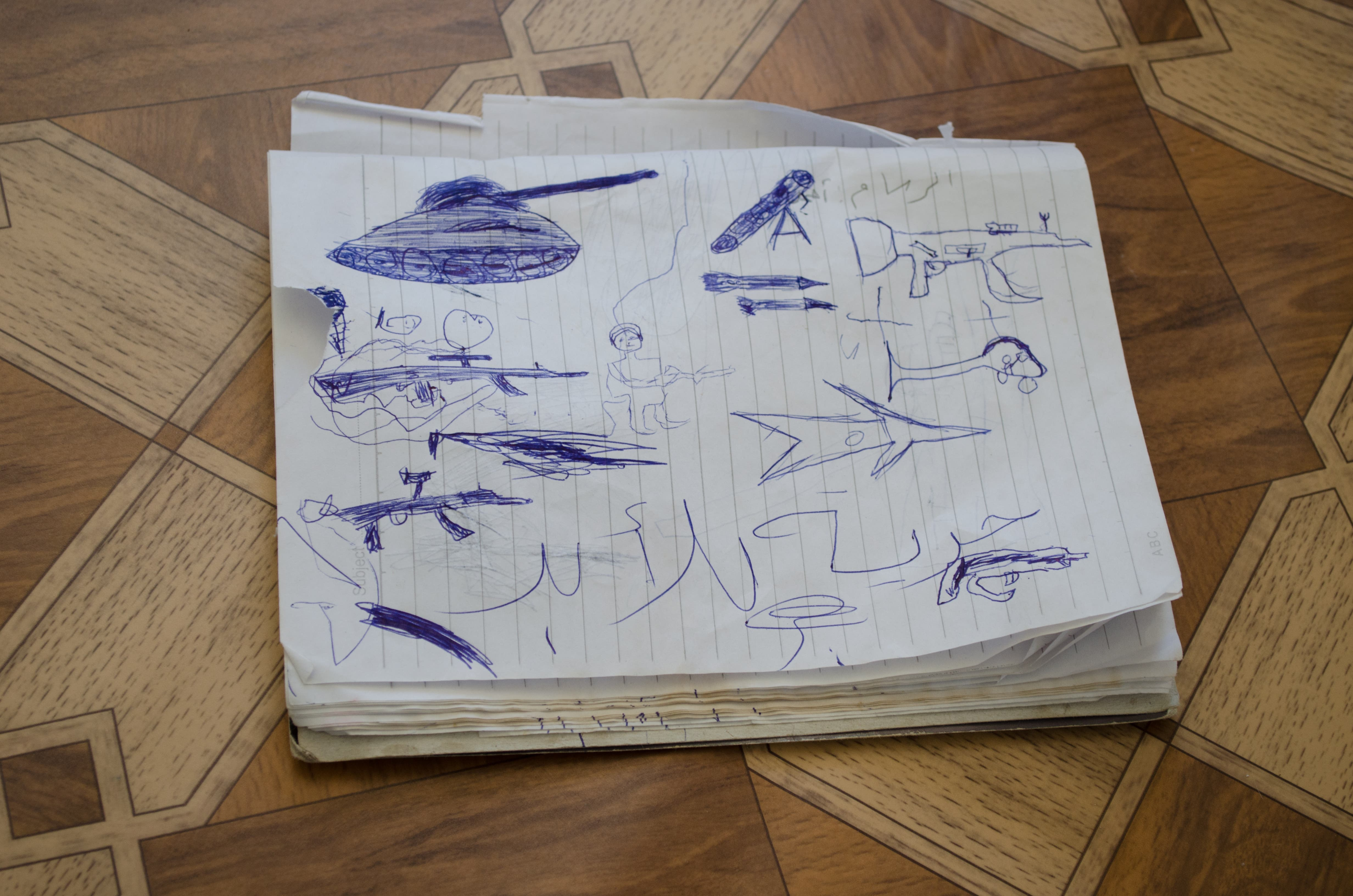 Soldiers, helicopters, tanks and rifles fill the notebook of five-year-old Ahmad al-Lubad. (Albawaba/J. Zach Hollo)