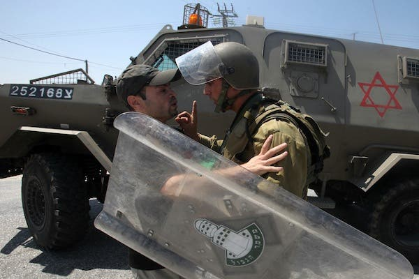 An Israeli soldier wags his finger at a Palestinian protester is seized by an during the evacuation of Palestinian protesters as they were trying to close the main road leading to the Israeli settlment of Efrata in the West bank town of Bethlehem on August 16, 2013 (AFP)
