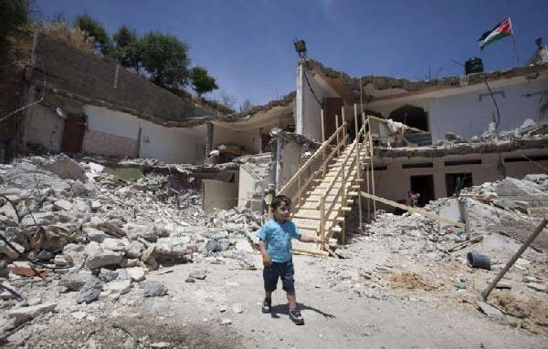 A Palestinian boy walks near the rubble of his family's destroyed house after Israeli bulldozers razed it down the previous day in the east Jerusalem neighborhood of Jabal Mukabbir in May. AFP Photo
