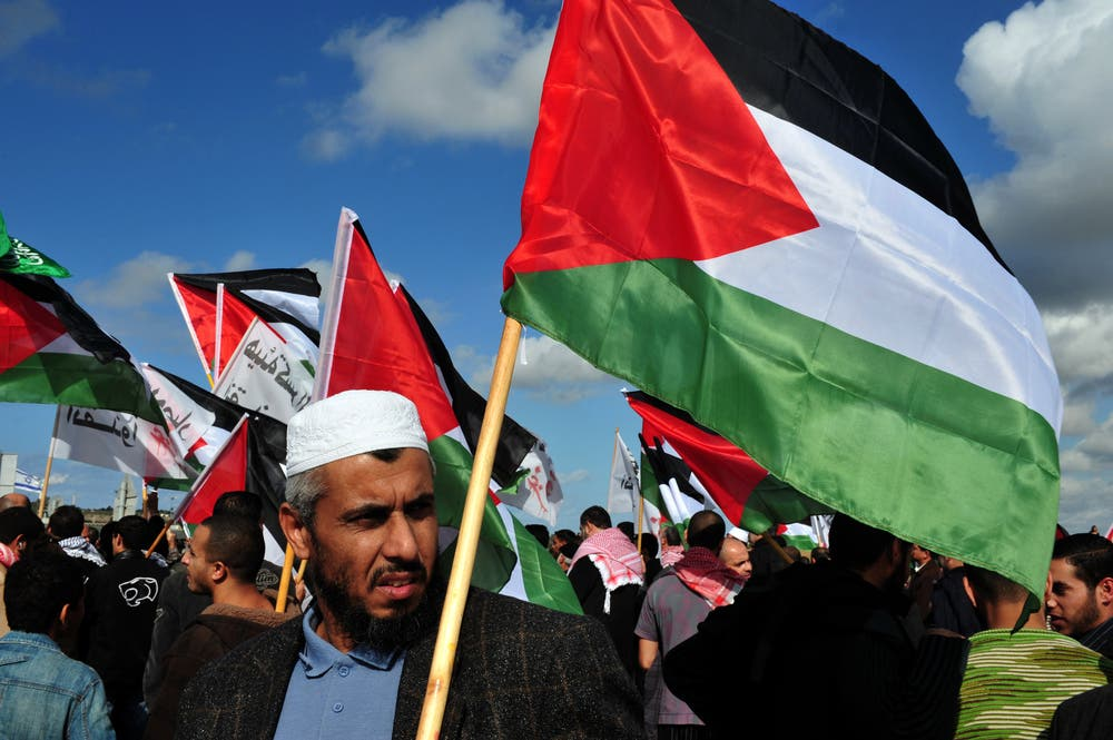 EREZ CROSSING-DECEMBER 31:Palestinian Arabs carry Palestinian flags during a protest on the Gaza-Israel border on Dec 31 2009. (Sutterstock/ChameleonsEye)