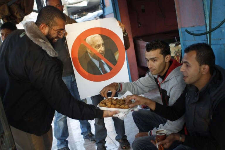 A Palestinian supporter of the Islamic Jihad distributes sweets in a street of the southern Gaza Strip town of Khan Yunis as a boy holds a poster bearing a portrait of former Israeli premier Ariel Sharon. (AFP)