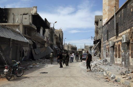 Syrian army soldiers assess a damaged street in the town of Qusair, in Syria's central Homs province on  Friday, as the regime sought to 'remove' all remaining rebel strongholds in the country. AFP