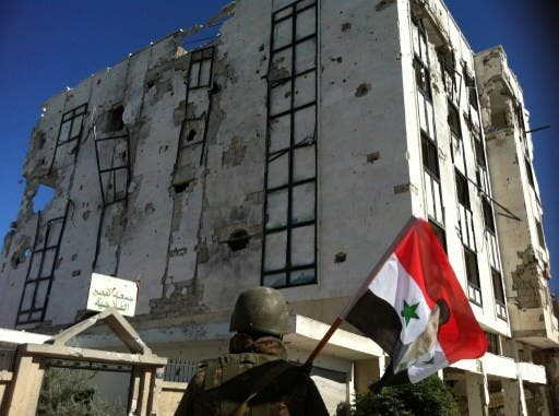 A Syrian army's soldier a national flag featuring Syria's President Bashar Assad in front of a building left in ruins with on Wednesday in Qusayr. AFP Photo
